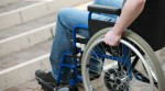 Ein Rollstuhlfahrer steht mit seinem Rollstuhl vor einer Treppe