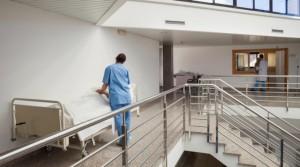 Krankenschwester mit Patient im Krankenhausflur