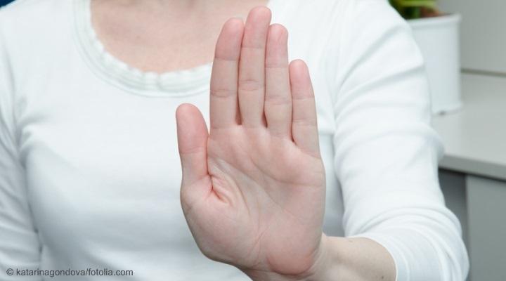 Frau, die ihre Hand abwehrend vor sich hält.