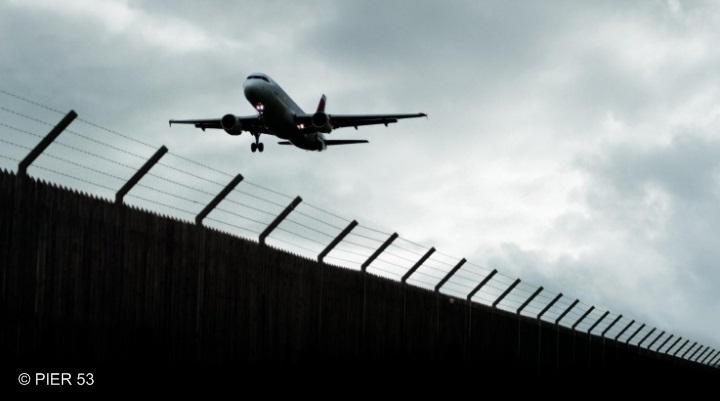 Flugzeug, das über einen Grenzzaun fliegt