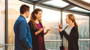 Drei Personen unterhalten sich in Gebärdensprache.