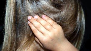 Kopf eines Mädchens, das sich das Ohr zuhält.