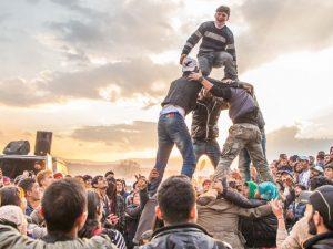 Flüchtlingslager Idomeni (Griechenland): Mehrere junge Männer bilden eine Pyramide, viele andere stehen drumherum, schauen zu und freuen sich.