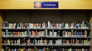 """Ein Regal mit Hörbüchern, über dem ein Schild """"Audiobooks"""" befestigt ist."""