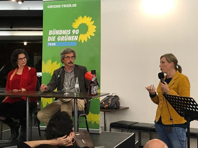 Susan Neimann und Winfried Thaa auf dem Podium, daneben steht Corinna Rüffer und begrüßt die Anwesenden.