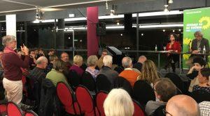 Im Vordergrund: Publikum, im Hintergrund: Susan Neimann und Winfried Thaa auf dem Podium.
