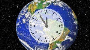 Erdkugel auf der eine Uhr abgebildet ist, deren Zeiger auf 5 vor 12 stehen
