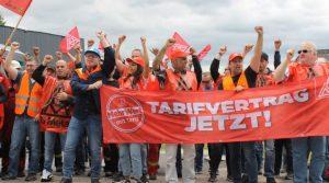 Streikende Beschäftigte des Riva-Konzerns mit rotem Plakat: Tarifvertrag Jetzt!