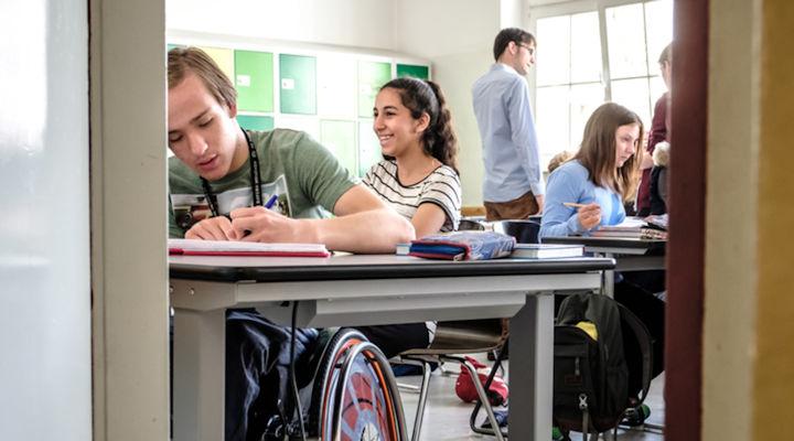 Blick in ein Klassenzimmer. Mehrere SchülerInnen sitzen an ihren Tischen, ein Mann steht.