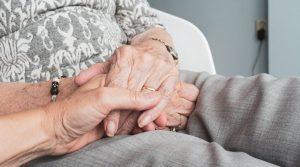 Eine ältere Frau hat ihre Hände im Schoß liegen und ein jüngerer Mensch hält ihre Hand.