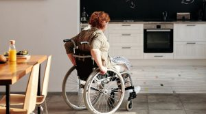 Eine Frau im Rollstuhl fährt vom Esstisch in die Küche.