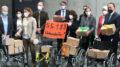 Corinna Rüffer und andere Abgeordnete stehen hinter 4 Rollstühlen, auf denen Pappkartons mit Unterschriften stehen. Die Abgeordnete Martina Stamm-Fibich hält ein rotes Schild hoch, auf dem steht: 55.188 Unterschriften