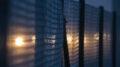 Ein hoher Maschendrahtzaun bei Nacht, hinter dem man diffuse Lichter erkennt.